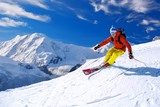 Skier skiing downhill in high mountains against blue sky - 91015610