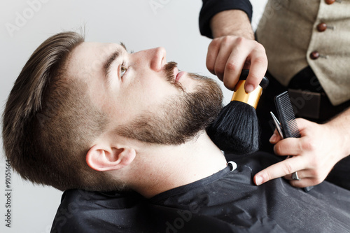 Fototapeta Barber cleaning face of his brutal customer with brush