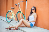 Sexy asian woman sitting near the wall and vintage bicycle