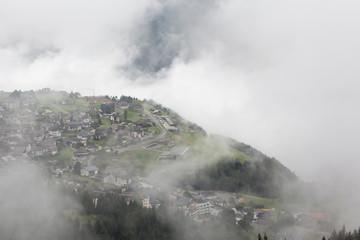 Nuages, vallée, et village de montagne