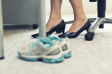 Fototapety Close up of a business woman sports shoes in an office