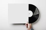 Fototapety Hand holding vinyl music album template on white wall background