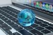Global computer network communication, internet business and marketing concept, blue transparent Earth globe on laptop keyboard macro view