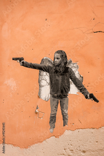 Poster graffiti of child gangster on orange wall