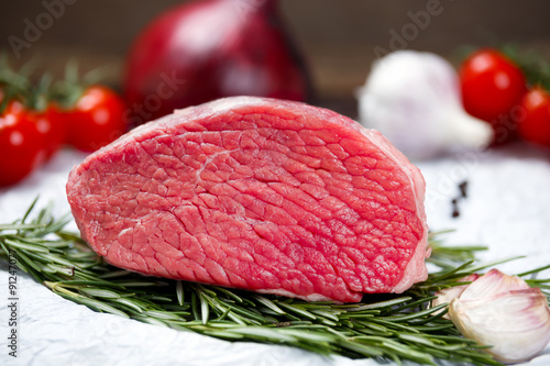 a pieces of fresh meat, beef slab, decorated with greens and vegetables Poster