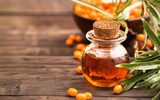 Sea buckthorn oil at right side of wooden background