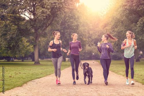 Deurstickers Jogging Gesundheitsbewusste Frauen laufen im Park mit ihrem Hund