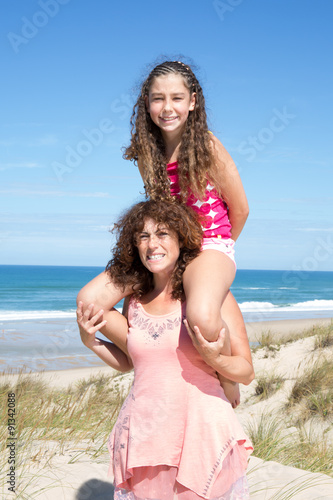 Young girl sits astride on the shoulders of her mother Poster