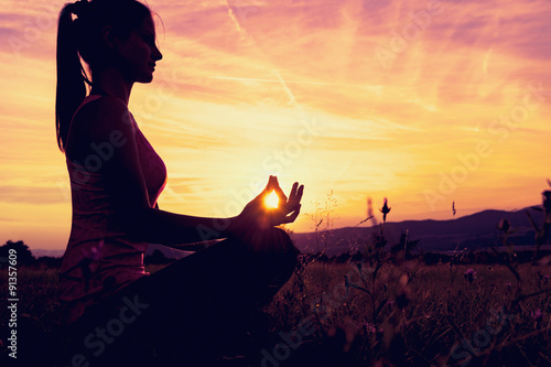 Fototapeta Young athletic woman practicing yoga on a meadow at sunset, silhouette