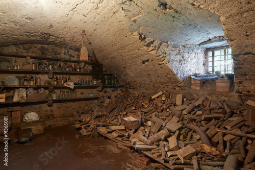 In de dag Old, dark basement with wood pile in ancient house