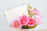 Fototapety Pastel Coloured Artificial Pink Rose in flower pot and white pap