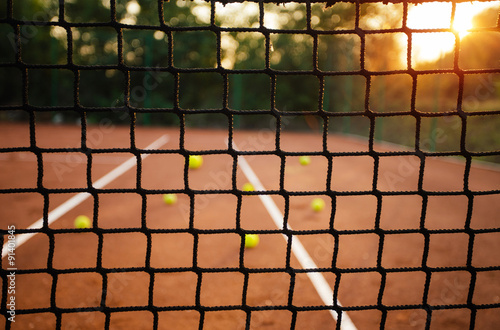Fototapeta Close up of tennis net with balls in background