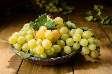 Cesto di uva bianca su piano di legno, luce pennellata