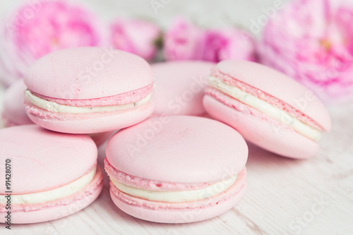Fotobehang Macarons Gentle pink macaroons with rose on wood