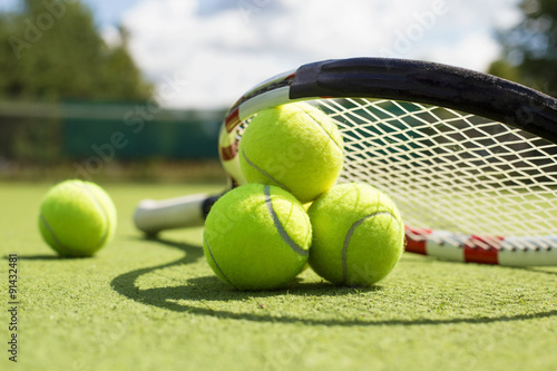 Poster Tennis balls and racket on the grass court
