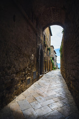 Passage under the walls of Italian village in Tuscany, Pienza