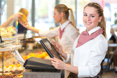 Shopkeeper at bakery working at cash register