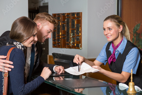 receptionist at hotel showing guest something on map