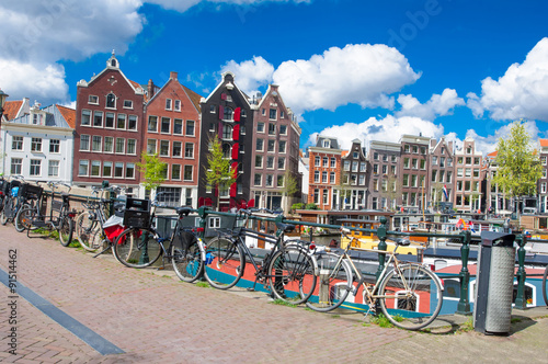 Poster Amsterdam, the Netherlands-April 27: Amsterdam cityscape with apartment houses and bikes parked on the bridge on April 27,2015