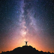 Man and the Universe. A person is standing on the top of the hill next to the Milky Way galaxy with his hands raised to the air.