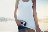 Woman wearing white vest with camera