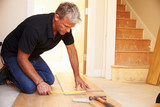 Man laying wood panel flooring during a house refurbishment poster