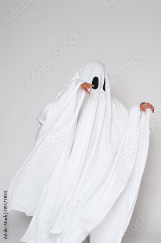 Poster young child dressed in a ghost costume for halloween
