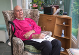 95 years old English man in domestic interior, reading local life magazine. Health, care and medicine concept
