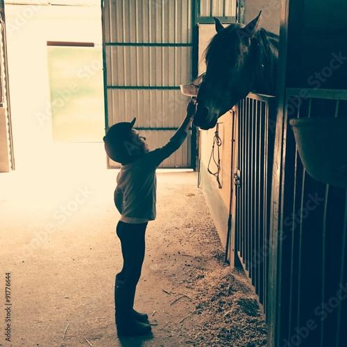 Zdjęcia na płótnie, fototapety, obrazy : Niña acariciando caballo en el establo