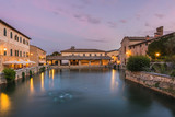 Fototapety View on thermal bath in the medieval Tuscan town at dusk.