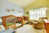 Nursery room with yellow and blue walls and two cribs.