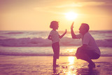 Father and son playing on the beach at the sunset time. - Fine Art prints