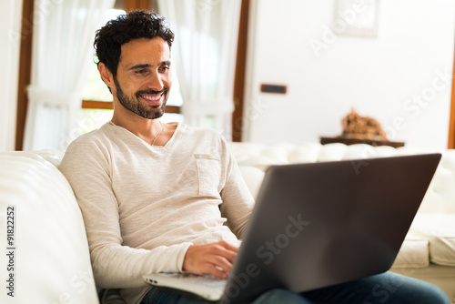 Man using a laptop computer in his apartment