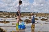 Fototapety Une mère et sa fille cherchent de petits crabes à marrée basse