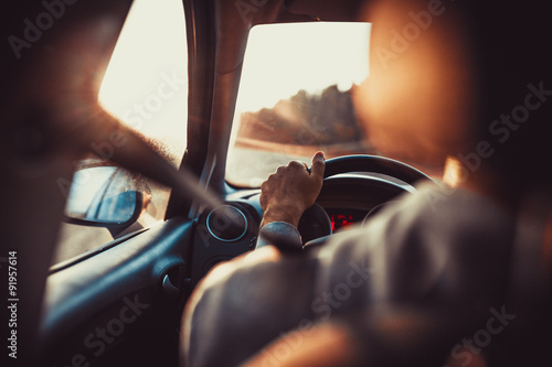 Man driving car, hand on steering wheel, looking at the road ahead,sunset. - 91957614