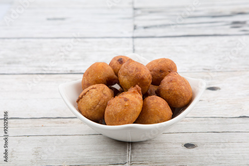 poster of Popular Malaysian fritter snack deep fried banana balls or locally known as Cekodok Pisang in white bowl