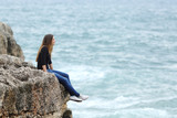 Casual woman sitting in a cliff watching the sea - Fine Art prints
