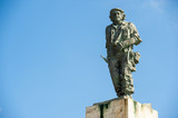 Statue of Cuban revolutionary Che Guevara stands in blue sky at a mausoleum dedicated to him and other fighters from the revolution poster