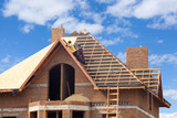 House under construction. Workesr installing fibreboard on the roof - 92104273