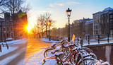 Fototapety Sunrise over the canal streets of Amsterdam, the Netherlands, with bicycles covered in snow on a beautiful winter day. HDR