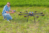 Man with multicopter on ground poster