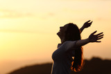 Fototapety Back light of a woman breathing raising arms