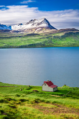 Small cottage in the mountains above the fjord in Iceland © shaiith
