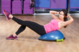 Athletic girl does exercises on a bosu ball in gym