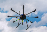 Multicopter in flight on sky and clouds background poster
