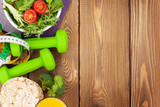 Fototapety Dumbells, tape measure and healthy food over wooden table