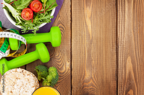Tuinposter Gymnastiek Dumbells, tape measure and healthy food over wooden table