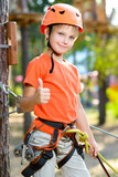 Fototapety Cute boy shows thumb up with climbing equipment in an adventure