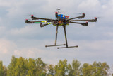 Multicopter in flight on trees background copter poster