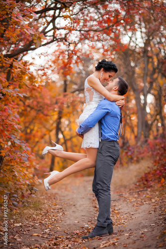 Poster Oranje eclat Smiling couple hugging in autumn park. Happy bride and groom in forest, outdoors